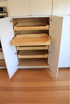 Modern kitchen pantry pullout shelves, white cabinets and wood floors