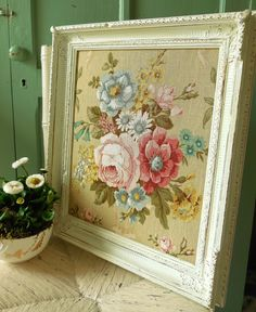 Vintage floral linen stretched in a chipped painted antique frame....