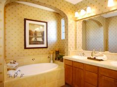 This farmhouse master bathroom is both charming and serene. The pleasant focal point in the space is the oval tub that is nestled within a cozy arched cove.