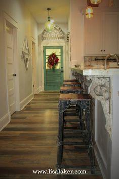 Eclectic farmhouse, eclectic entry, vintage door color, antique corbels, teal door, eclectic decorating, iron bar stools, vinyl plank flooring, weathered wood flooring