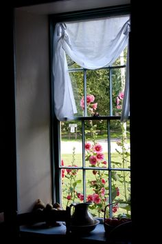 country window with hollyhocks...