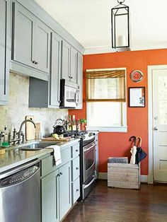 Contrasting Color Scheme  Blue-Gray + Burnt Orange  Cool blue-gray cabinets help tone down the spicy orange walls in this kitchen. The hue of the cabinets subtly reflects light streaming in from the windows, helping the small space feel larger.