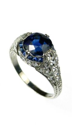Antique sapphire and diamond ring: Cushion shaped sapphire, the bombe platinum mount with a calibre sapphire line around he sapphire, a line of French-cut diamonds to each shoulder and diamond sides. At SJ Phillips.