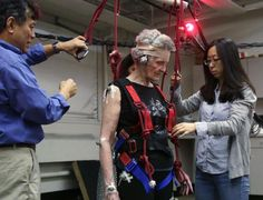 This July 28, 2014 photo shows Clive Pai, a University of Illinois-Chicago physical therapy professor, left, and graduate student Emma Wang, right, hooking Mary Kaye, 81 into a safety harness before she demonstrates a treadmill balance session at the school in Chicago. Once in the harness, Kaye walks on a lab-built walkway that causes people to unexpectedly trip and can teach them quickly how to catch themselves and avoid falling. Falls in the elderly cost $30 billion yearly to treat and can…