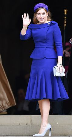 Princess Beatrice looked chic in a royal blue Ralph & Russo suit skirt and a deep purple Sarah Cant hat, finished off her sophisticated ensemble with towering grey heels, and a matching boxy clutch bag, as she arrived at younger sister Princess Eugenie's wedding at St George's Chapel, Windsor Castle