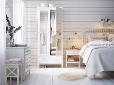 Stort soveværelse i landlig stil med et hvidt garderobeskab med spejldøre, en hvid kommode med et hvidt spejl ovenover, et hvidt sengebord og en stor, hvid seng.