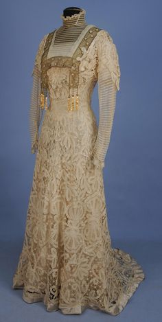 TRAINED BATTENBURG LACE HIGH NECK GOWN, c. 1902. Cream lace over silk with curving bodice having striped net long sleeve and neck insert edged in metallic gold net with beaded tassels. B-38, W-30, front L-58, back L-68. (Broken brides, silk lining shattering, small holes to net)