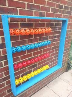 wooden frame, washing line and airflow balls in different colours to make an outside abacus