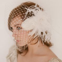 Silk Organza feather fascinator  / Birdcage blusher veil 744. $255.00, via Etsy.