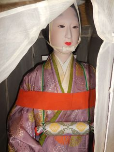 A Heian lady on pilgrimage, wearing a kakemamori (懸守り) amulet about her neck, and travelling costume or tsubosōzoku: comprised of a large, veiled hat (ichimegasa), informal robe (kouchigi) and a red taboo sash (kakeobi).