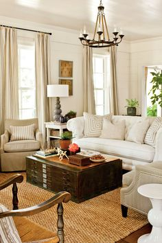 A tufted chesterfield sofa covered in family-friendly Sunbrella fabric adds scale and traditional style. Tip: A large sofa needs large pillows—ours are 26 inches square.  Editor's Tip: Reinvent vintage finds in a new setting. Here, an old flat file cabinet works as a coffee table.  See more of the 2012 Farmhouse Restoration Idea House