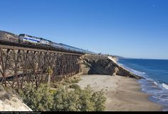 Amtrak 14, the northbound Coast Starlight, gallops across the trestle and over the beach at Gaviota with a couple oddball engines for power.