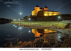 Stock Photo: Night scene with medieval castle by the lake in Finland. The moon shining on clear night sky and reflection of the castle in the water.