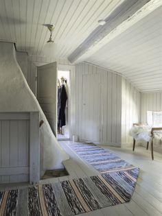 Till vänster om den mysiga hallen ligger matsalen. Innanför finns köket, som bär spår av renoveringen på 50-talet. Den gamla vedspisen värmer fortfarande upp köket. Till höger om hallen finns ett gästrum och innanför ligger det ljusa vardagsrummet.  Hela ovanvåningen är målad med samma grå färg. Murstocken trängs bredvid den speciella trappan, där de första stegen är i tegel för att sedan övergå i trä.