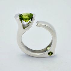 Snake - A modern sophisticated limited edition. This ring brings art deco to this century. The curves are flawless on this piece making it comfortable and fashion forward. Sunroesilver.com The center stone is faceted  Peridot and measures 8.5cm round. There is a side stone mounted on each side. Limited Edition.925 Sterling Silver.  #sunroe #Peridot #snake Peridot, Amethyst, Bottle Opener, Fashion Forward, Snake, Art Deco, Silver Rings, Sterling Silver, Curves