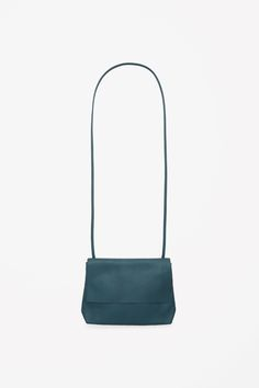 Made from lightly grained leather with clean raw-cut edges, this compact shoulder bag has a flap-over front and metal zip fastening. With a cotton-lined main compartment and flat pocket on the back, it has a slim strap that can be adjusted with an inside toggle.