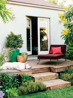 A rustic deck...This raised deck off of a bedroom at this Los Angeles, CA home creates a perch for an oversize lounge chair, whose cushion echoes the bronzy brown foliage of a spiky-leafed phormium near the deck's front edge. Bronze plants repeat near each garden room, reinforcing the brown-red theme. (Photo: Coral Von Zumwalt)