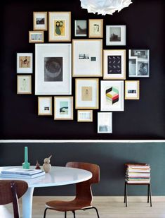 Une salle à manger chic avec une grappe de cadres sur un fond noir.