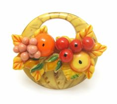 A lovely vintage celluloid basket of fruit and leaves brooch. #vintage #jewelry #brooch
