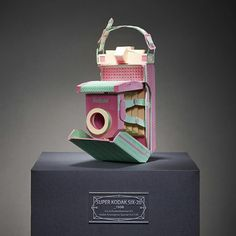 Korean artist Lee Ji-heebuilds paper models of old film cameras, recreating the details of their every mechanism through expertly folded paper. Although his paper cameras match the original in every aspect of their form, the colors he selects for his designs are much different. Instead of matching