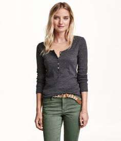 CONSCIOUS. Fitted top in organic cotton jersey. Slightly lower-cut neckline with decorative scalloped trim. Buttons at front, long sleeves, and rounded hem.