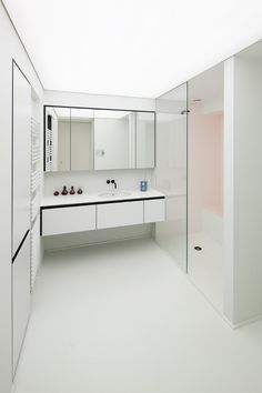 Bathroom: white concrete floor and walls, frameless floor-to-ceiling fixed single-panel shower screen, wall-mounted full-width handleless cabinet vanity, full-width mirror cabinets, bulkhead, custom joinery