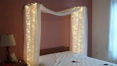 DIY pseudo canopy with delightful lights. Pinterest win! Took about an hour. Used swing out curtain rods, curtains for fabric (on sale at bed bath and beyond), and white wire xmas lights. I cut small slits in the curtains and used zip ties to keep the lights on the rods and hidden between layers of fabric.