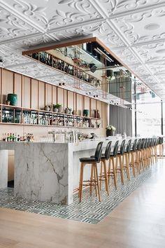 Inspiratie! Prachtig wit plafond met ornamenten. Gecombineerd met licht eiken en marmer. Wat een geweldig horeca interieur. Een mooie combi met de stalen plafondbekleding van New York Ceiling Co. - www.newyorkceiling.nl #hospitalityinteriors #newyorkceilingco