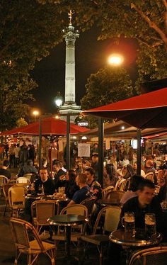 Stop by the Place de la Bastille at night and visit the square's cafés, bars, night clubs, and concert halls. #Paris #nightlife #cafes