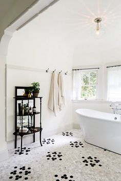 Vintage-inspired bathroom with honeycomb tile, a freestanding tub, and a retro pendant light