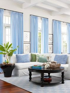 I like the blue curtains paired with the grey walls? bhg  COLOURS GREAT..CURTAINS HUNG HIGH W PICS BETWEEN.WHITE COUCH... LOVE IT