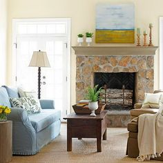 Country style leans casual but can be given a sophisticated vibe with a few contemporary elements. This stone fireplace is decidedly country, but the abstract artwork above the mantel lends a modern edge. Although stylistically different, the artwork blends with the room, thanks to its color palette. The blues, greens, and yellows in the painting pick up on the hues on the sofa, throw pillows, and accessories.