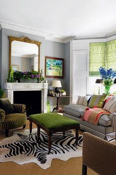 A small grey living room with bay window and green blinds in the home of Butter Wakefield. Small space design ideas.