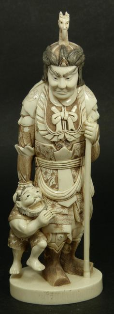Japanese hand carved ivory netsuke depicting standing warrior holding Oni demon to right hand. Meiji to Showa Period.