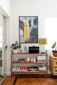 living room styling, book shelf, big art, white walls and wood floors.