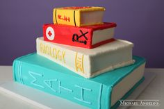 School Books #43Graduation  This cake is made in the shape of stacked books. It is perfect for any type of graduation celebration. Each layer is iced in buttercream and decorated to look like the real thing.