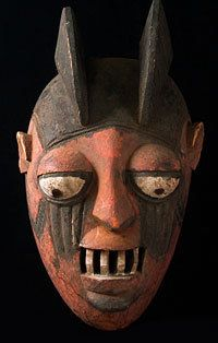 Yoruba people, Nigeria  16.2 inches, painted wood  It's a big helmet mask made to be worn at a slight angle, with the dancer seeing through the mouth. Red and black painting with unusually large white teeth. This Egungun mask is obviously from a Yoruba area, possibly Owo or Akoko. Shows wear from use and age, including a repair at rear edge and white touch up to the eyes and teeth.