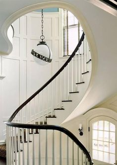 Cottage home features a winding staircase lined with board and batten walls illuminated by a black and white globe lantern.