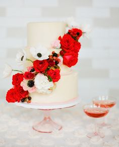 3 Tier white cake with mixture of white & red cascade flowers.  // Featured: The Knot Blog