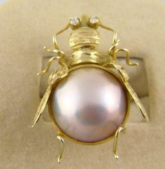 Fabulous 1950's 14 Kt Gold with Large Mabe Pearl Figural Bee Cocktail Ring. Approx. size 7, face is a bit over 1 by 1 1/2 inches, pearl is approx. 1/2 inch and weighs 7.6 grams. Fabulous look and so detailed. Etched and brushed gold wings and body. Two small diamond eyes. Stunning large mabe pearl body with a pink caste.
