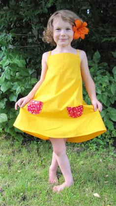 Little sun dresses! Way adorable (and the little girl is the perfect model)! If any pattern-altering-savvy person out there is able to help me alter the pattern for a big girl, I'd love to hear from you!