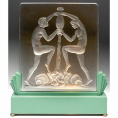 """Unusual Frederick Carder lighted sculpture, clear glass panel with deeply etched design of water bearers, held by a green enameled metal base, 11.5""""w x 13""""h"""