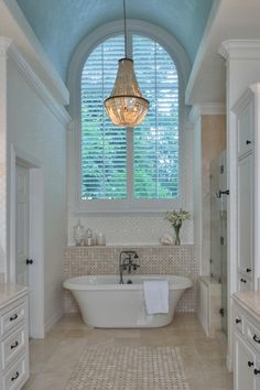 This luxe master bathroom features a traditional freestanding bathtub, elegant chandelier, arched window and his and hers vanities on either side. Neutral tile flooring and a textured light blue ceiling adds subtle contrast to the space.