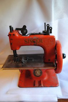 VINTAGE CHILDS 1950'S SINGER RED SEWING MACHINE - I used to have one of these when I was a kid.  It would really sew a simple seam.