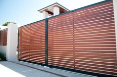 Double sliding smartwood (faux timber) slat driveway gates from Fencemakers