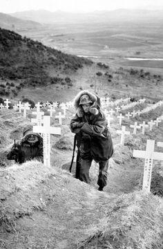 Korean War U.S. Marine visits grave of South Korean soldiers, Korea, 1951.