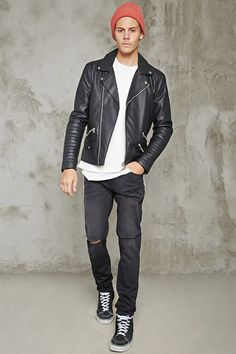A faux leather moto jacket featuring long sleeves with zippered cuffs and ribbed detailing, snap-button notched lapels, an asymmetrical zip front closure, an interior chest pocket, a mini snap-button flap pocket at the front hem, two zippered front pockets, one zippered front accent, and a center-back seam construction.