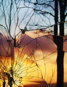 As lindas fotografias com pores do sol vistos através de espelhos quebrados de…