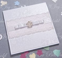 Simple but elegant design created with a layer of embossed tapestry card, lace, ribbon and finished with a pearl and diamanté embellishment. One of the many simply elegant designs from www.ajoytobehold.co.uk