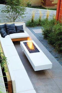 Feuerstelle aus Beton und um herum Sitzmöglichkeiten mit Polster